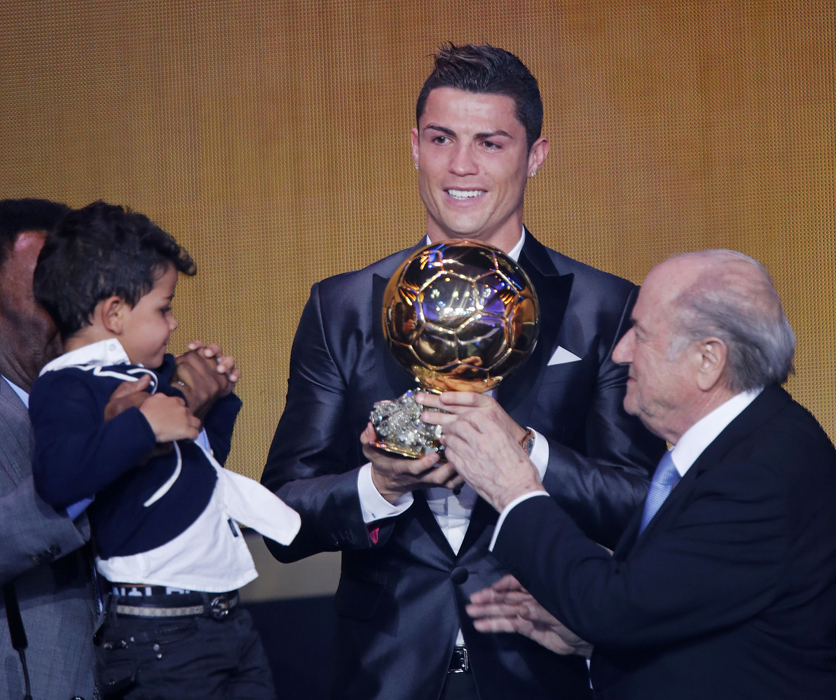 Real Madrid's world player Christiano Ronaldo of Portugal, center, FIFA President Joseph Blatter and Ronaldo's son Ronaldo Ju