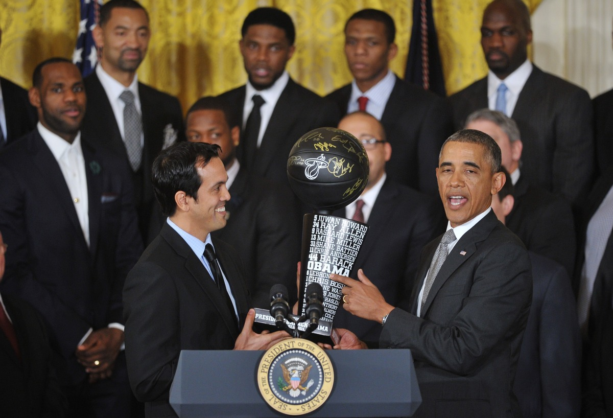 US President Barack Obama (R) receives a commemorative trophy from Miami Heat head coach Erik Spoelstra (L) during an event h
