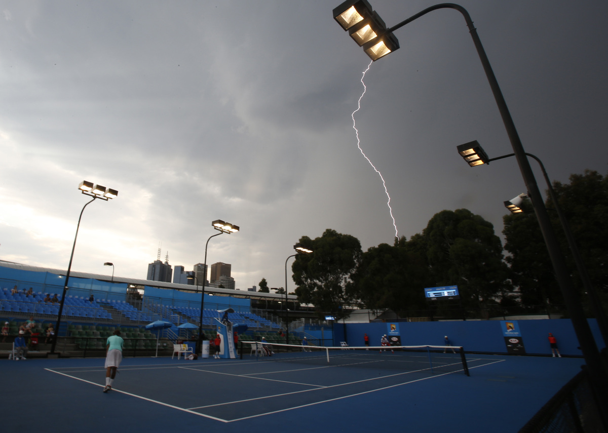 The lightning is seen in the sky at an outside court at the Australian Open tennis championship in Melbourne, Australia, Thur