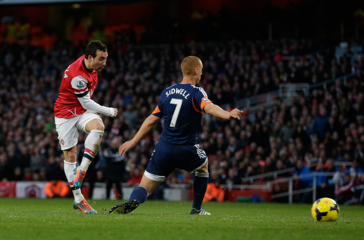 Arsenal's Santi Cazorla, left, scores his side's second goal past Fulham's Steve Sidwell during the English Premier League so