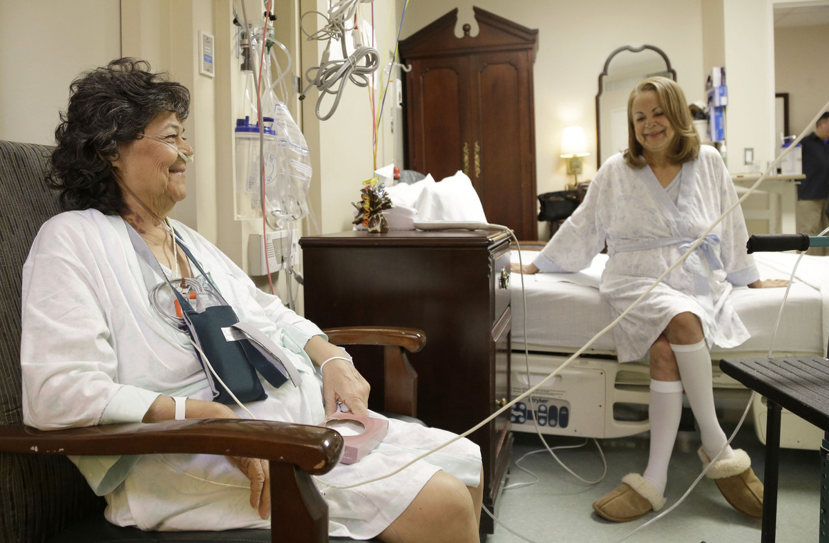 In this Jan. 14, 2014 photo, Irma Myers-Santana, left, and her sister Anna Williamson visit in Williamson's hospital room in