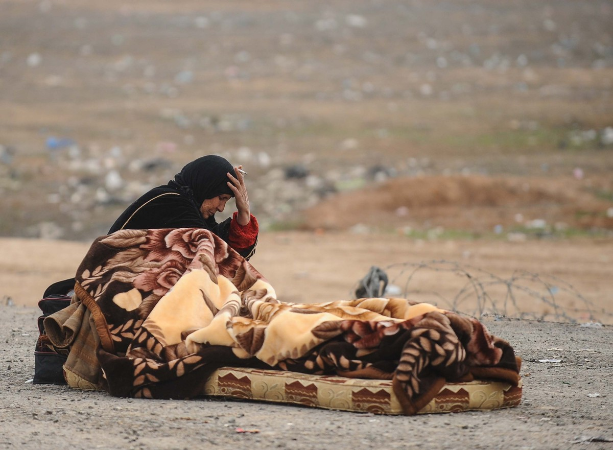 A Syrian woman smokes as she waits on the Syrian side of the border to pass into Turkey on January 23, 2014. (Photo by Ercin