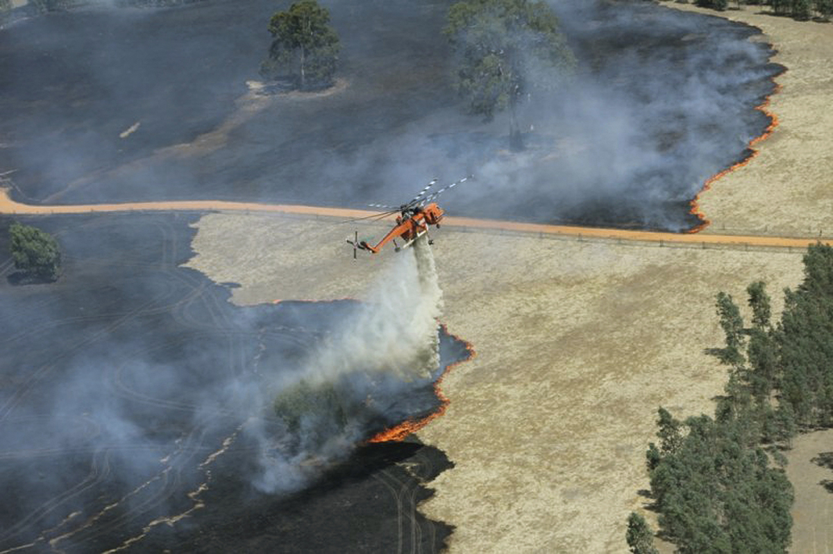 In this image released by Victoria Country Fire Authority, a water bomber works to extinguish a large fire burning throughout