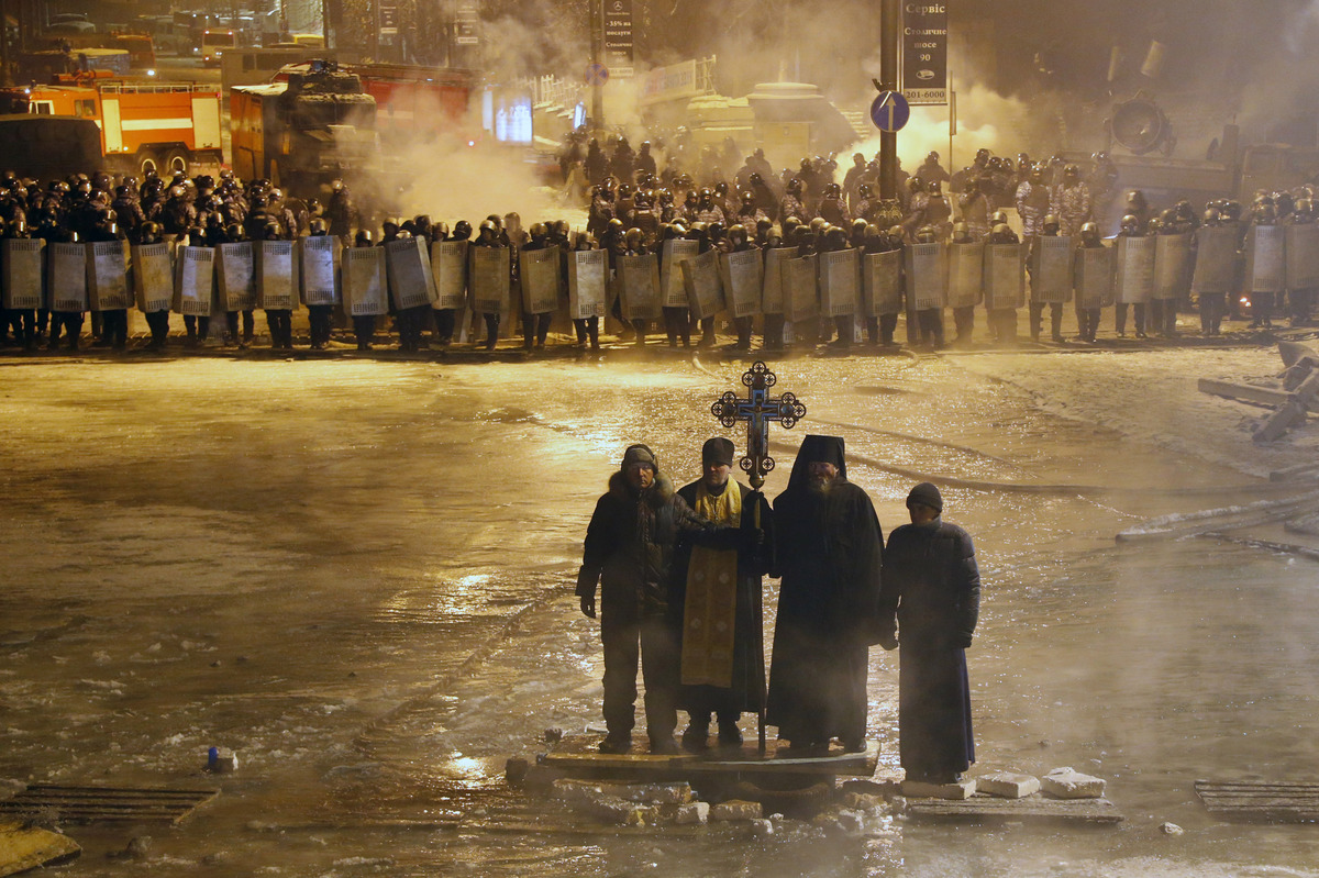 Orthodox priests pray as they stand between pro-European Union activists and police lines in central Kiev, Ukraine, early Fri