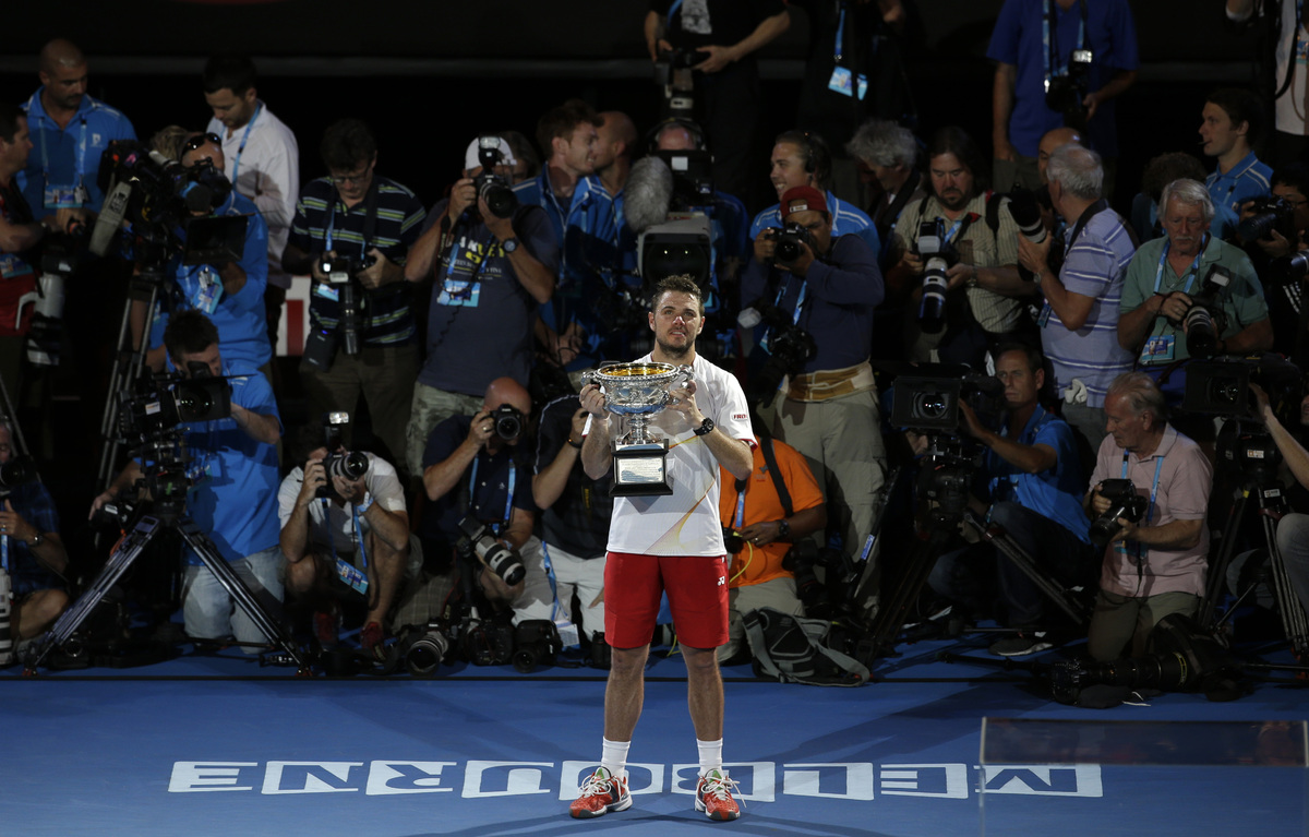 Stanislas Wawrinka of Switzerland holds the trophy after defeating Rafael Nadal of Spain in the men's singles final at the Au