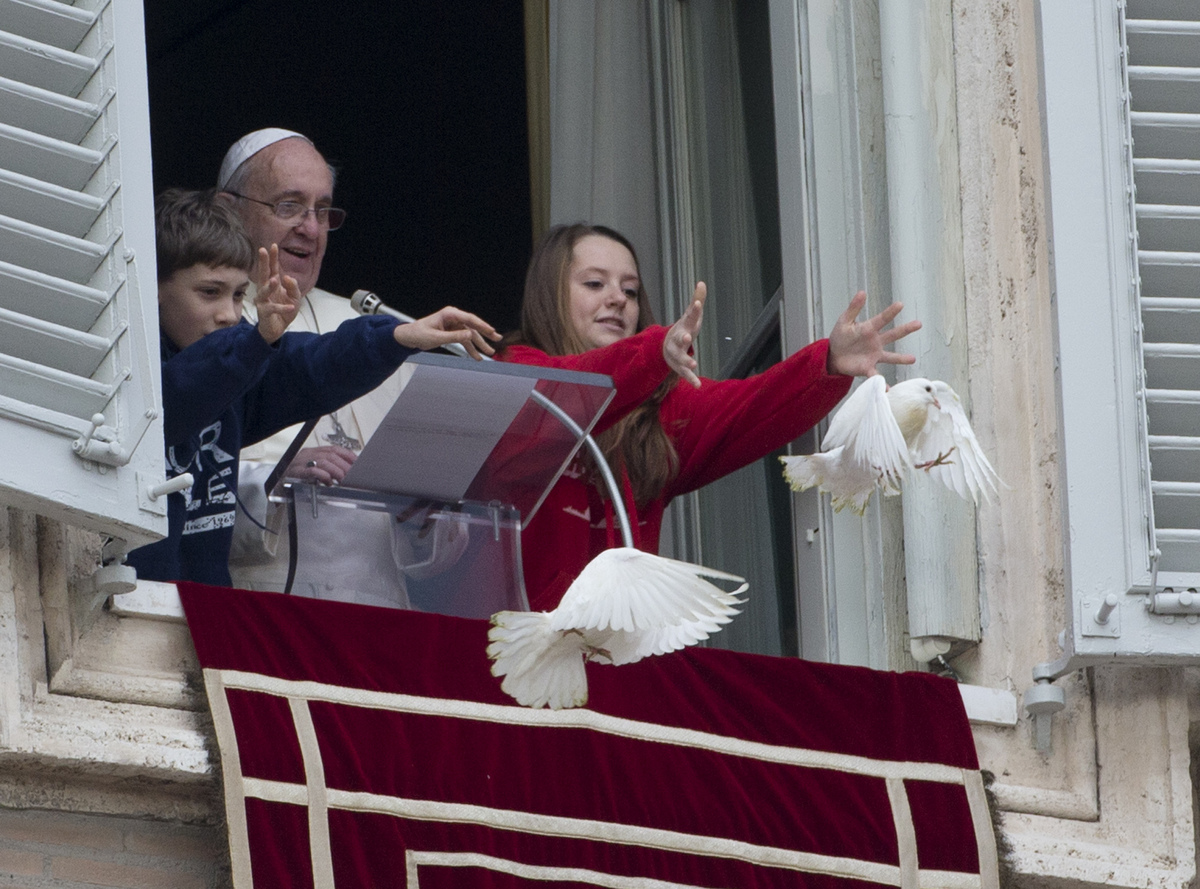 Pope Francis looks at two children as they free doves during the Angelus prayer he celebrated from the window of his studio o