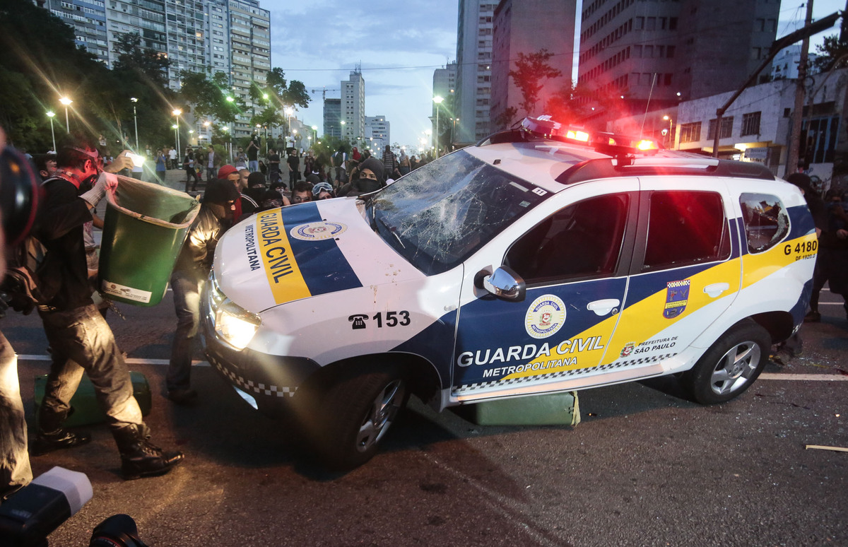 A civil guard car is attacked by demonstrators during the 'Nao Vai Ter Copa' (You are not going to have Cup) protest along Co