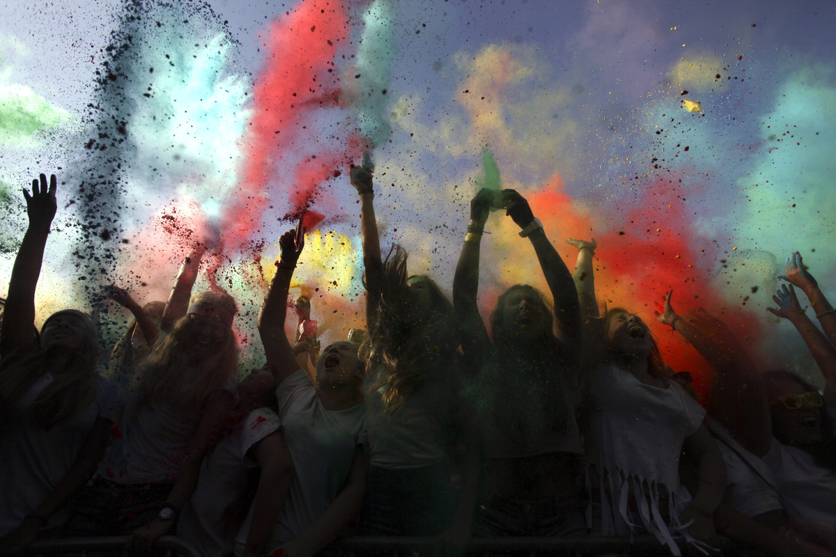 Revelers throw colored powders in the air during the Holi Festival of Colors in Lisbon, Sunday, Sept. 15, 2013. The festival,