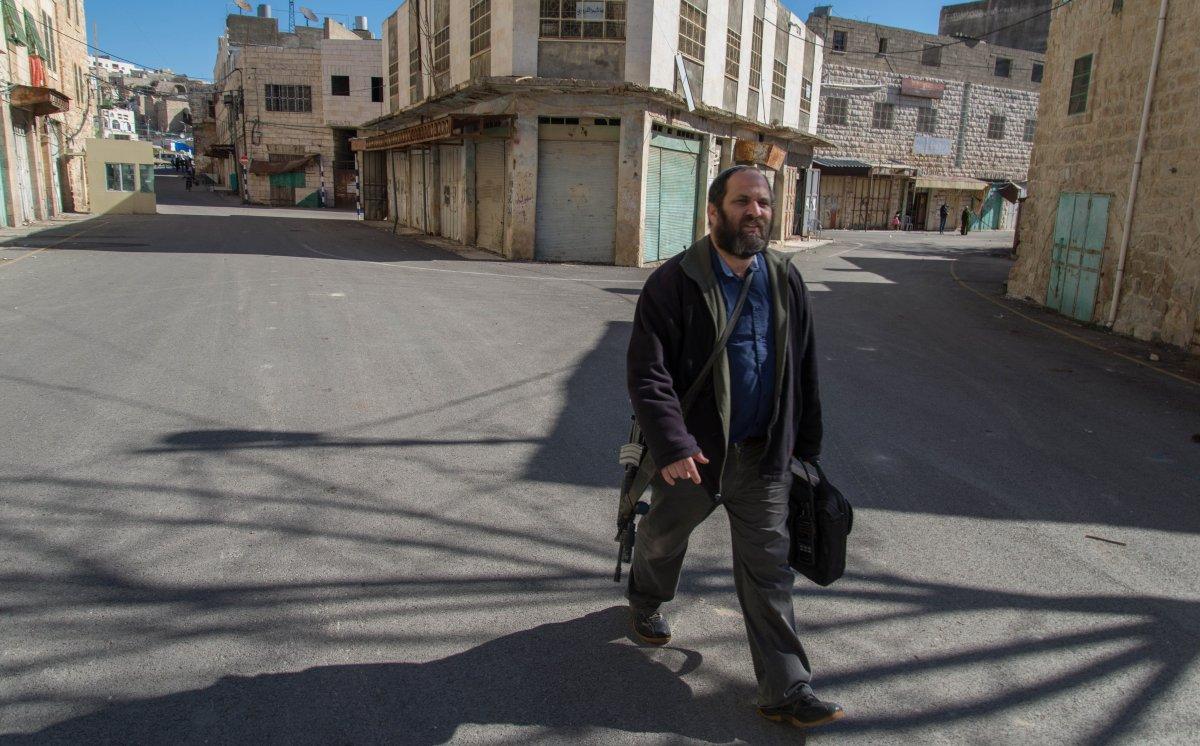 Armed Israeli settler strolls across checkpoint in Hebron, West Bank. (Photo: Thomas Dallal)