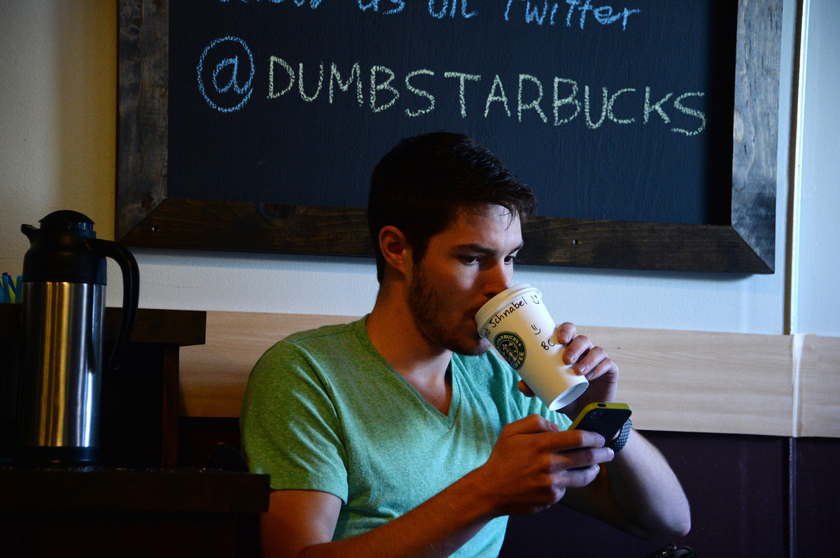Actor Tyler Schnable checks his phone inside 'Dumb Starbucks' coffee shop, February 10, 2014, in the Los Feliz area of Los An