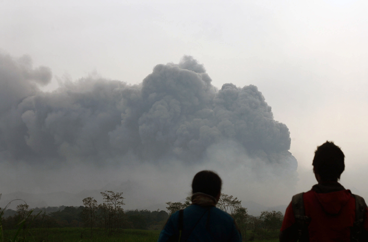 Residents watch the eruption of Mount Kelud volcano from Kediri town in East Java province on February 14, 2014. (JUNI KRISWA