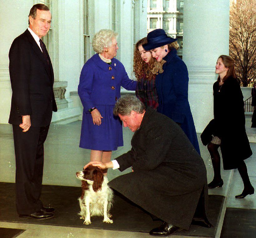 U.S. President George Bush (L) watches 20 January 1993 as U.S. President-elect Bill Clinton pets the Bush's dog Millie, as Fi