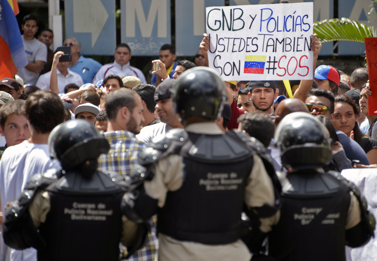 A student holds a sign reading 'Bolivarian National Guard and police, you are also Venezuelan. SOS' as he takes part in an an