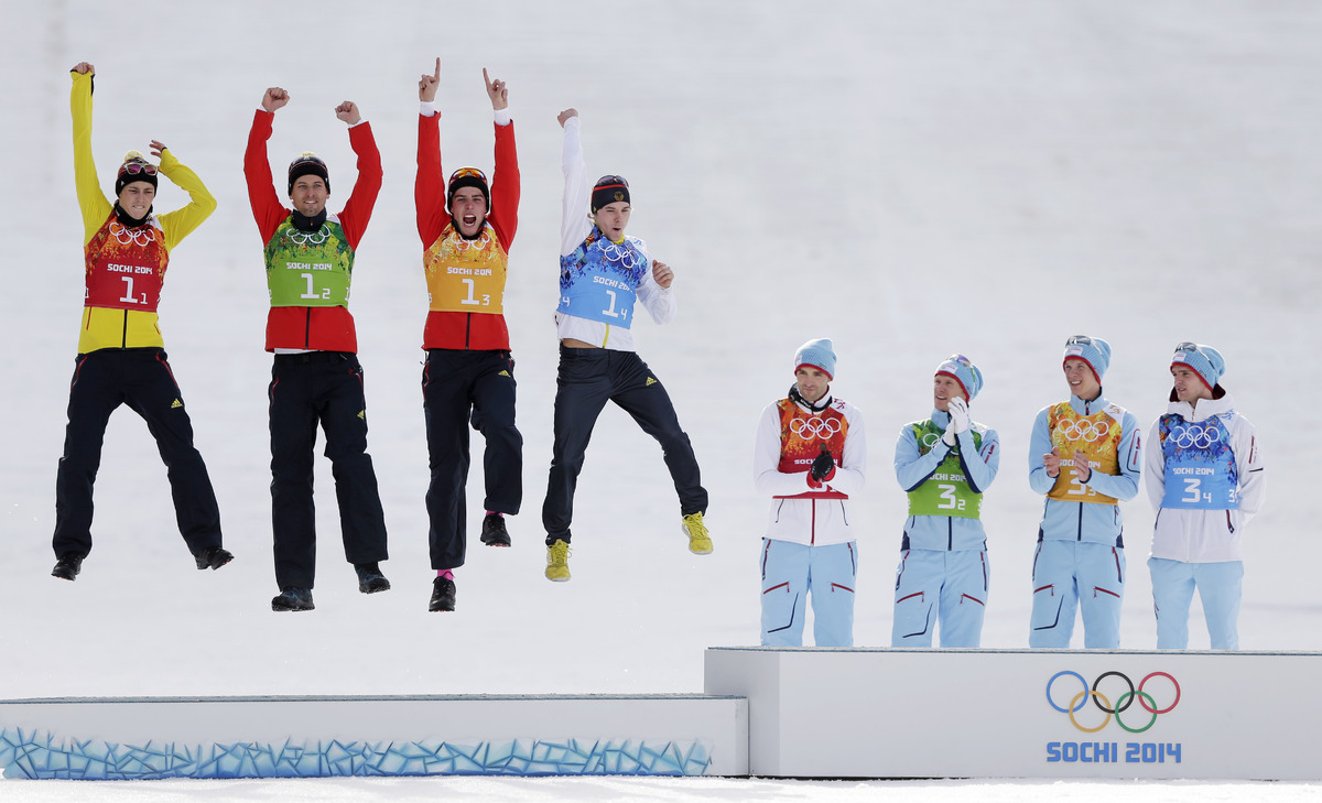 Germany's team celebrate winning the silver as Norway's gold medal winners applaud, during the flower ceremony of the Nordic