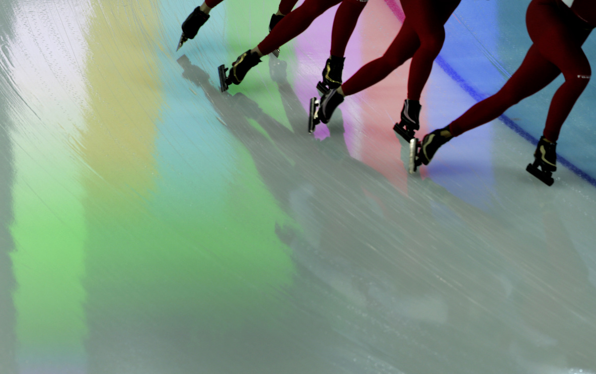 Polish speed skaters pass over a reflection on the ice from a screen above, during a training session at the 2014 Winter Olym