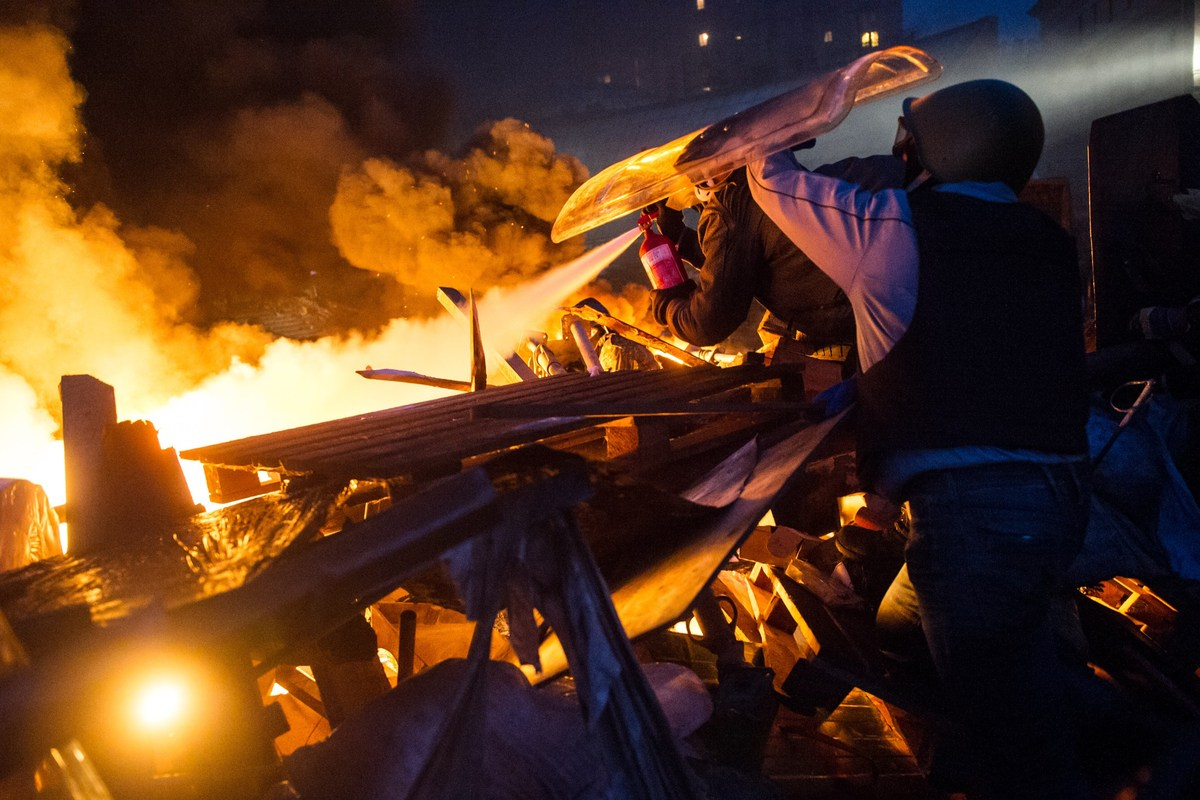 <br>Anti-government protesters stand behing their burning barricades during clashes with police in the center of Kiev on Feb.