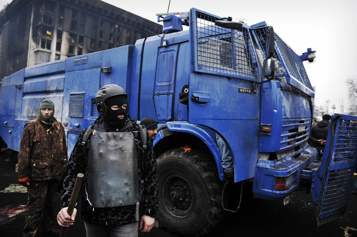 Anti-government protesters stand guard next to a police water cannon on the Independence square in Kiev on February 22, 2014.