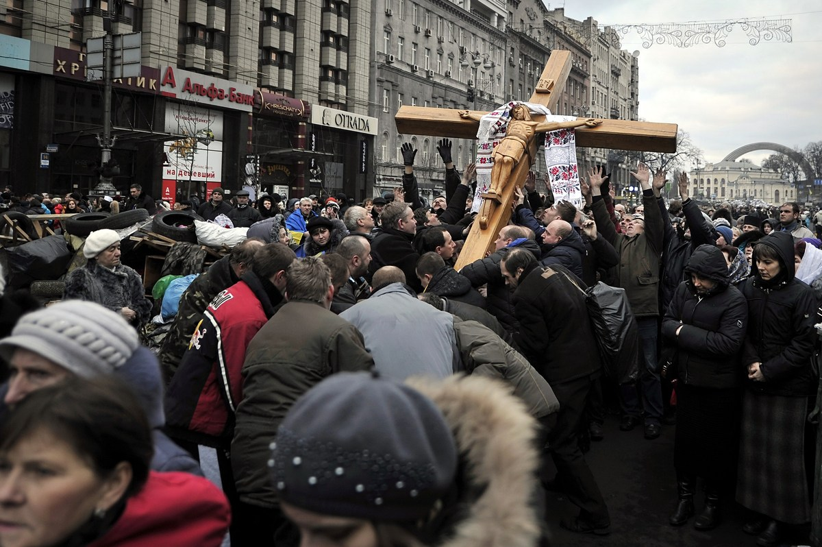 People lift up a large crucifix as they take part in a religious procession for the victims of recent clashes between protest