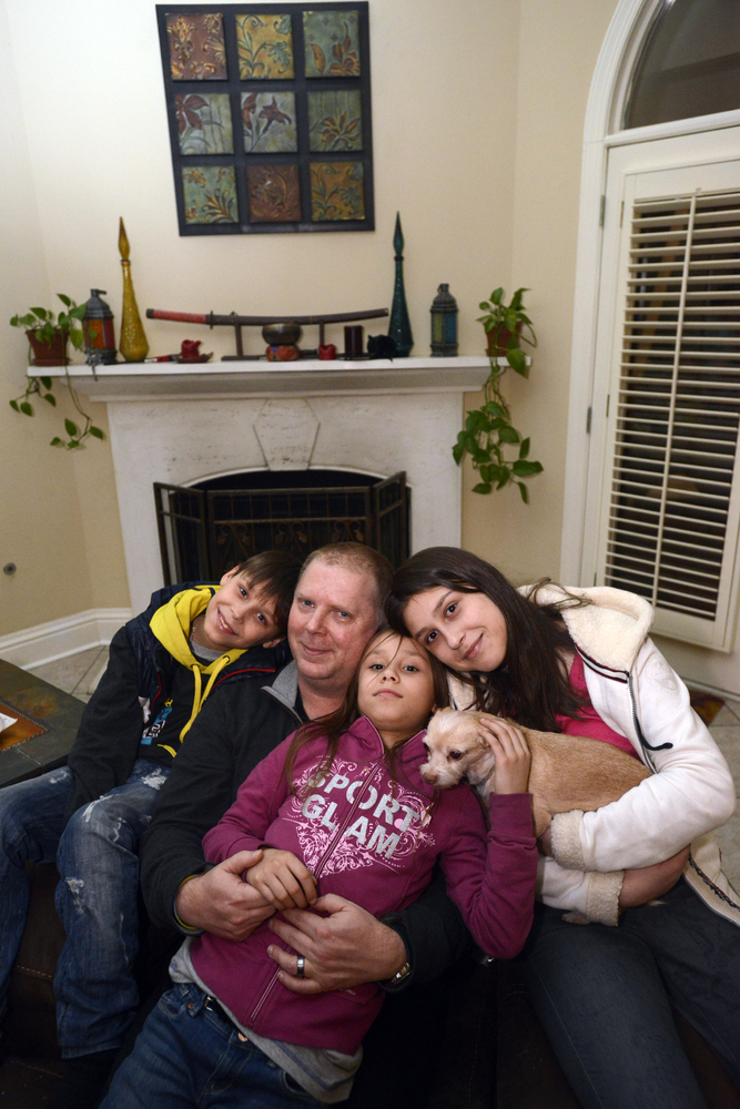 In this photo from Feb. 23, 2014, David Bundy arrives home to Montgomery, Ala., with three of their newly adopted four childr