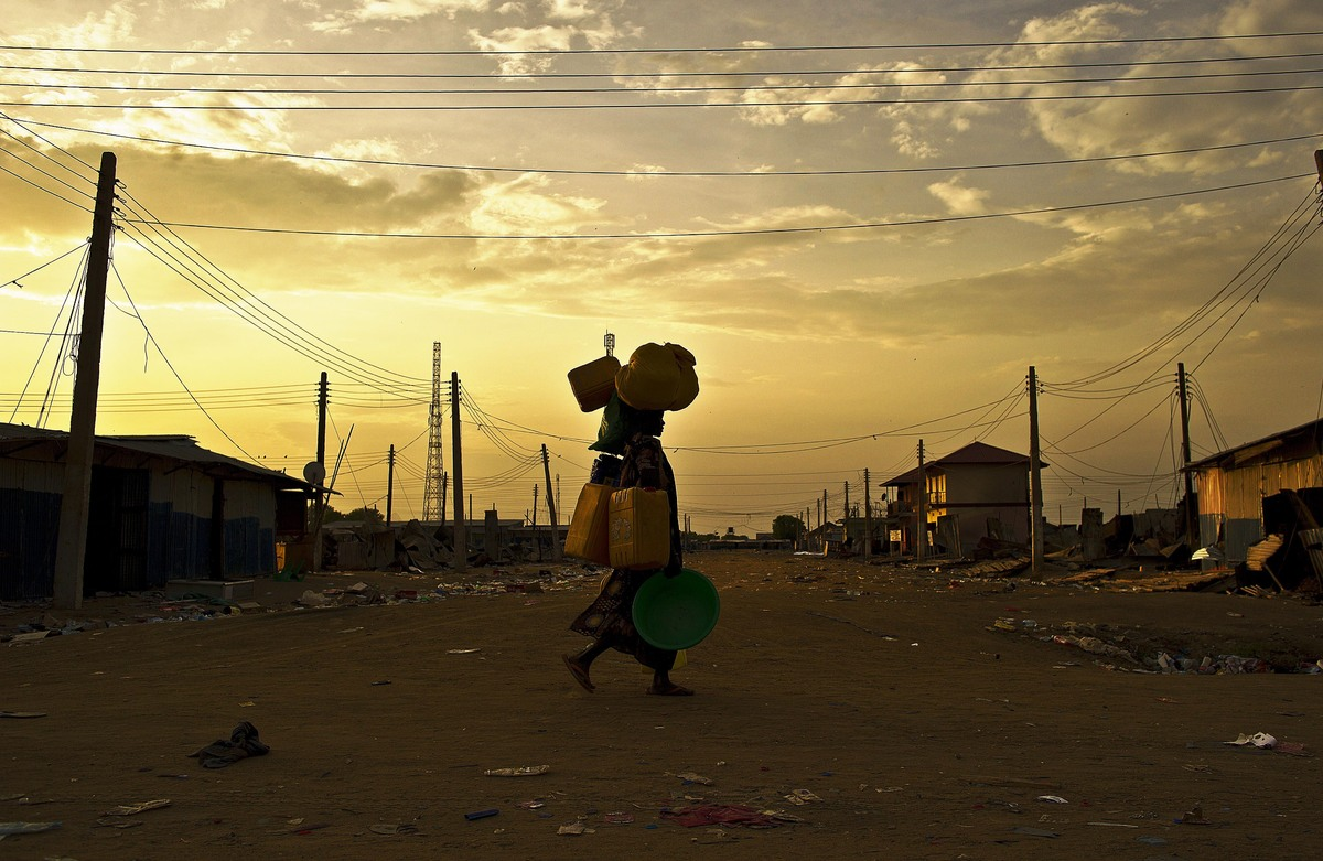 A woman carries belongings as she walks through a deserted street in Bor on February 1, 2014. (Carl de Souza/AFP/Getty Images