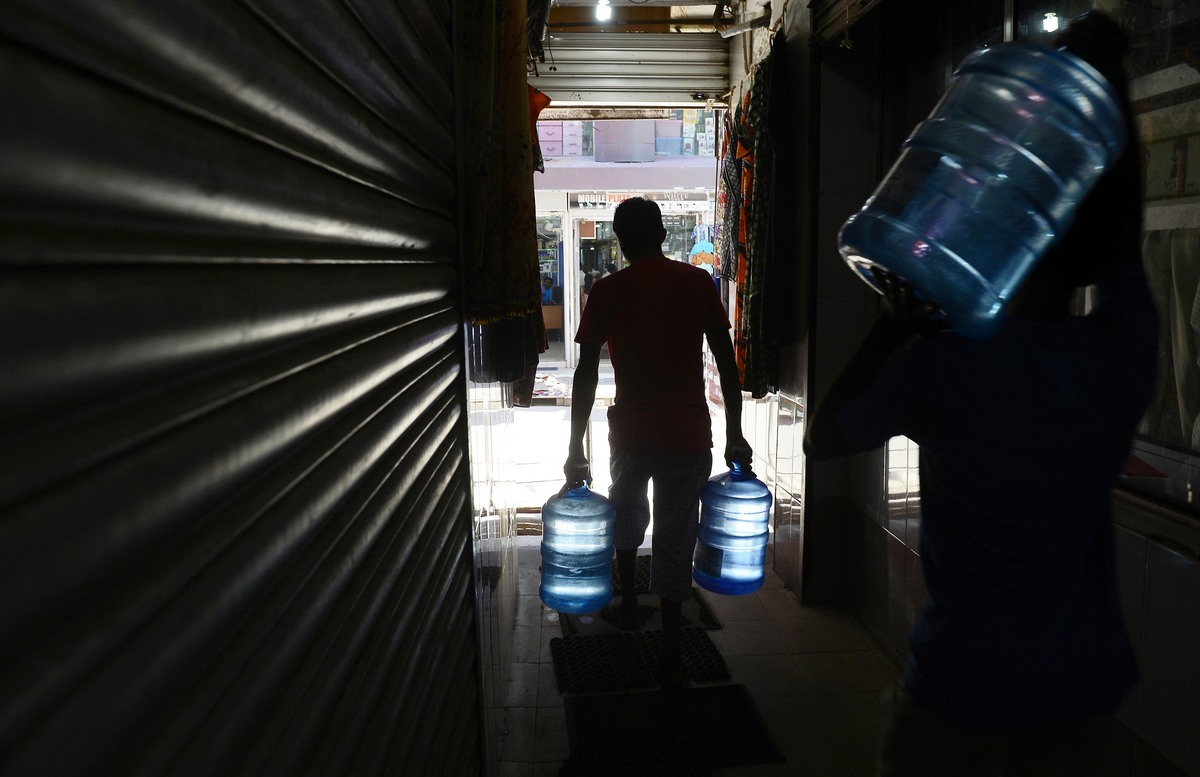 Sri Lankan laborers carry mineral water bottles at the main market in Colombo on October 29, 2013. (Lakruwan Wanniarachchi/AF