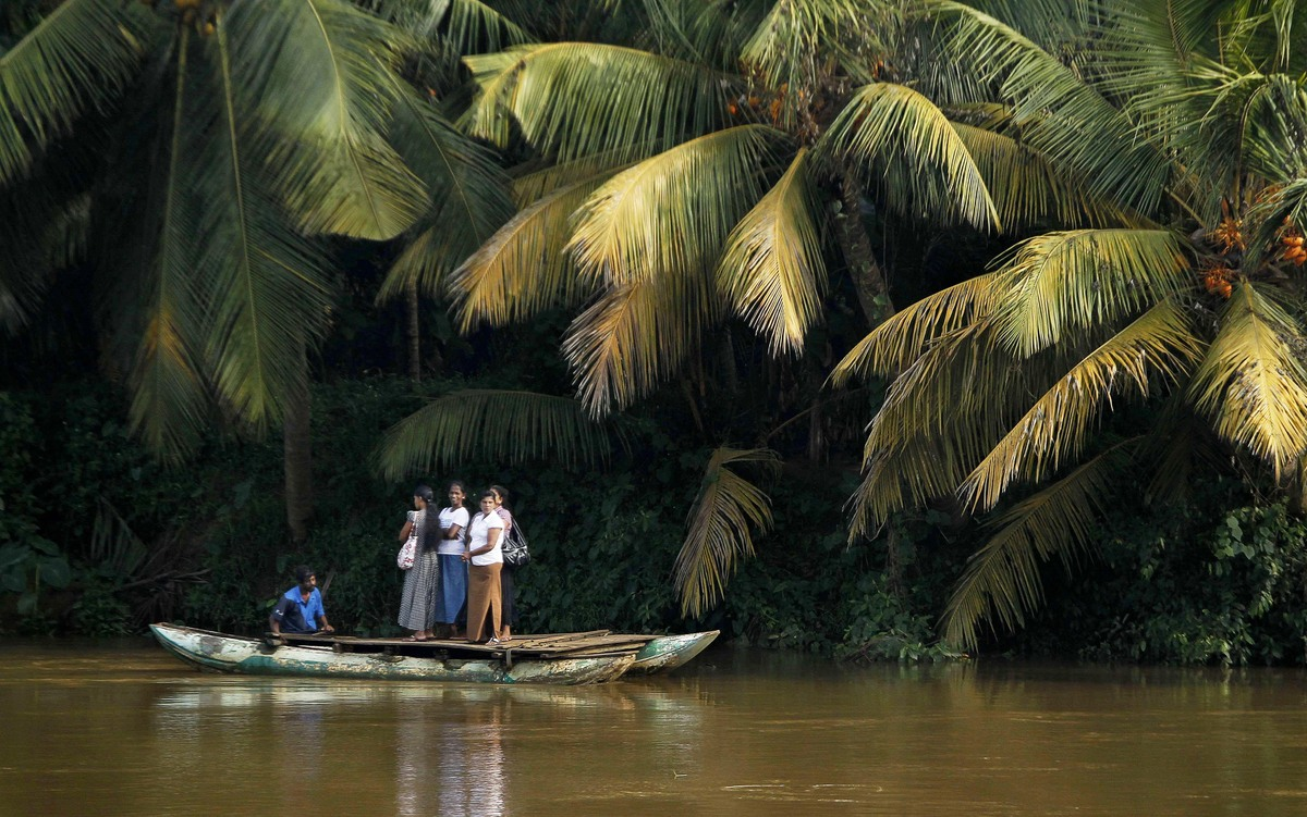 Sri Lankan women stand on a boat as they cross the Kelani river, in Colombo, Sri Lanka, Friday, Oct. 28, 2011. (Eranga Jayawa