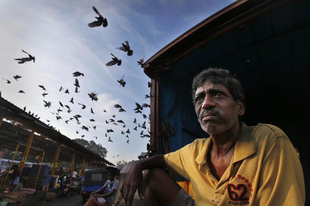 A daily wage laborer waits to be employed for the day at a market place in Colombo, Sri Lanka, Tuesday, Nov. 26, 2013. (Erang