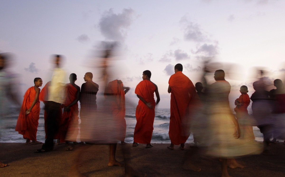 A group of young Sri Lankan Buddhist monks spend their evening at the sea front in Colombo, Sri Lanka, on May 8, 2012. (Erang