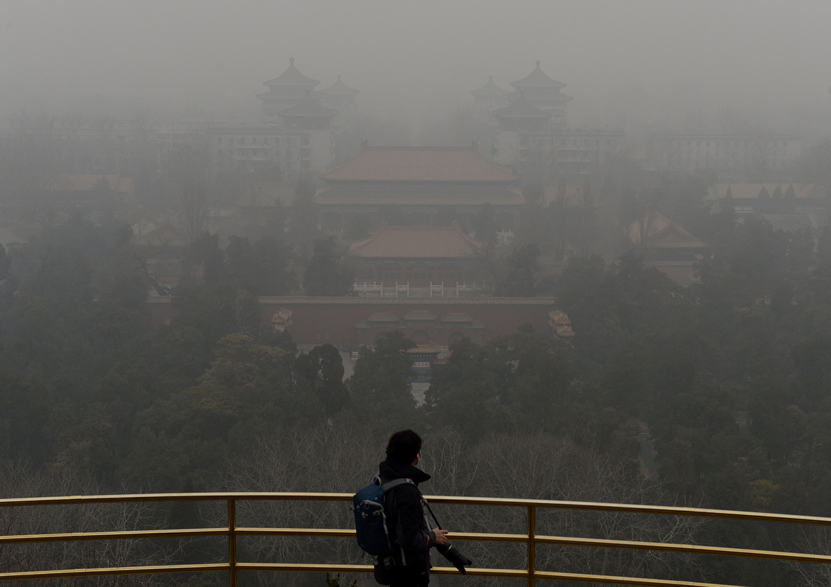 A tourist stands at the top of Jingshan Hill beside the Forbidden City as heavy air pollution continues to shroud Beijing on