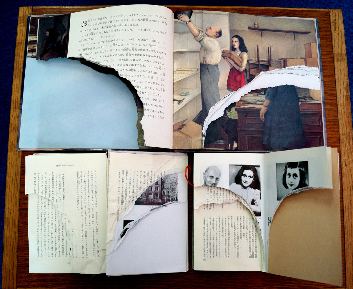 Ripped pages of three books of Anne Frank's 'Diary of Young Girl' are displayed at a library in Tokyo on February 21, 2014.