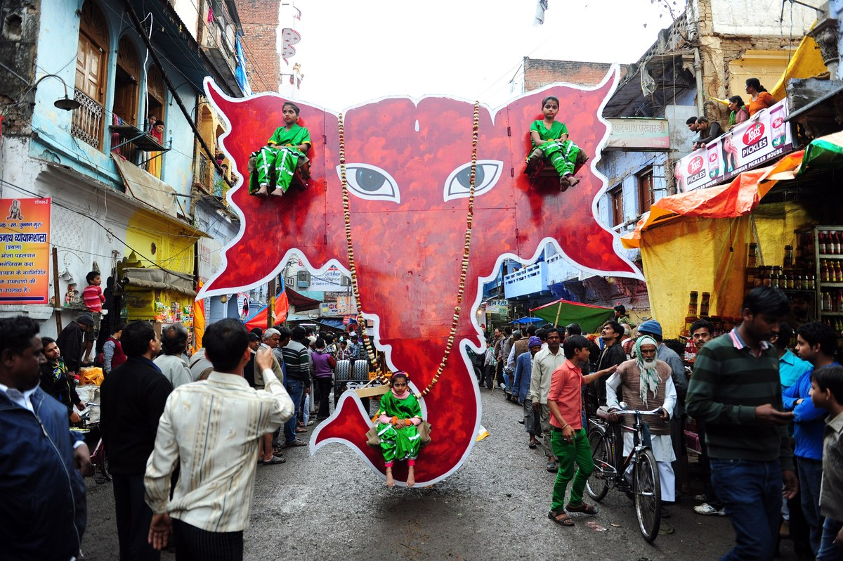 Indian children sit on an ornamental Ganesha head during a procession for Maha Shivaratri, dedicated to the Hindu god Lord Sh