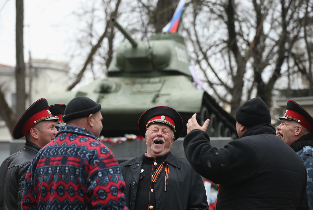 Pro-Russian Cossacks share a laugh next to a war monument at a gathering of pro-Russian supporters outside the Crimean parlia
