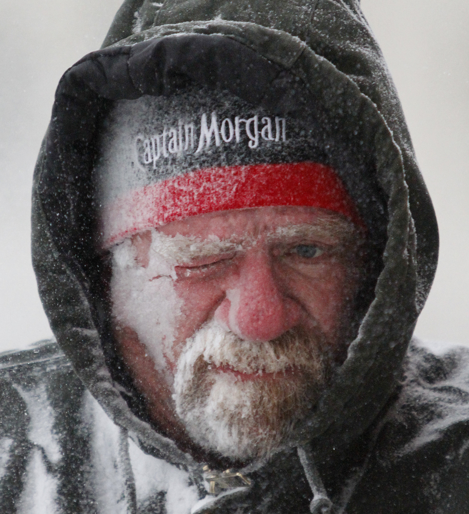 Allan Umscheid, owner of Yards By Al in Lawrence, Kan, feels the bitter wind and catches drifting snow on his face as he runs