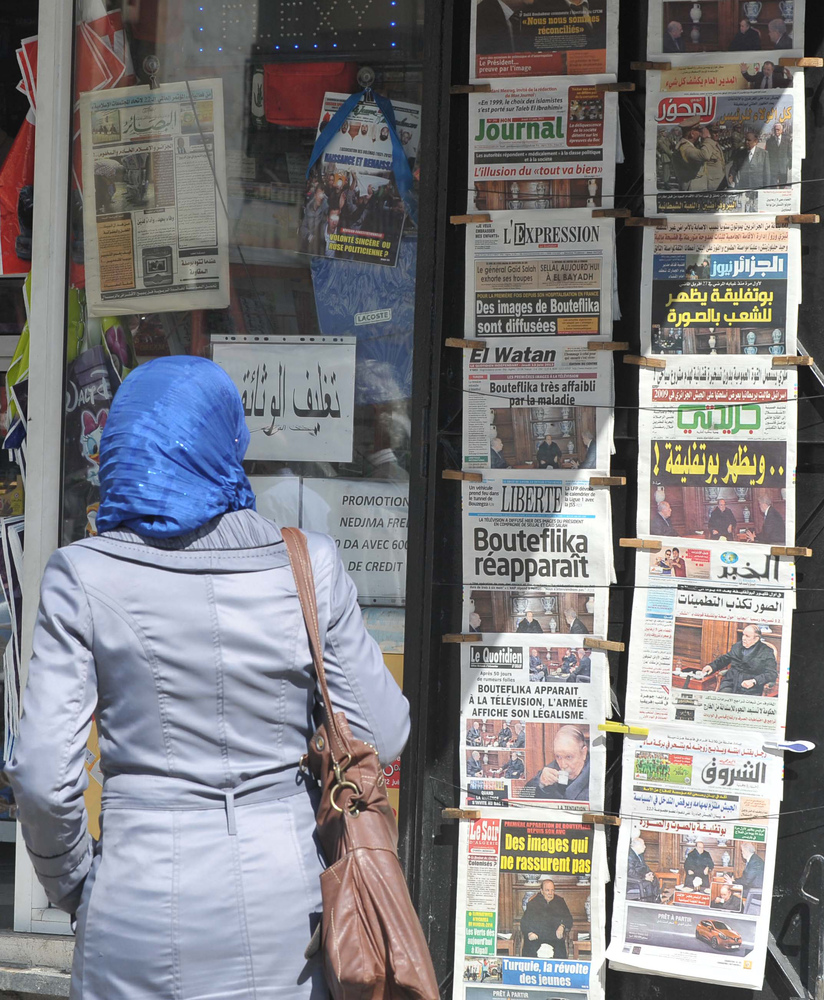 <em>An Algerian woman looks at the headlines of newspapers at a news stand in Algiers, Algeria, Thursday, June 13, 2013.(AP P