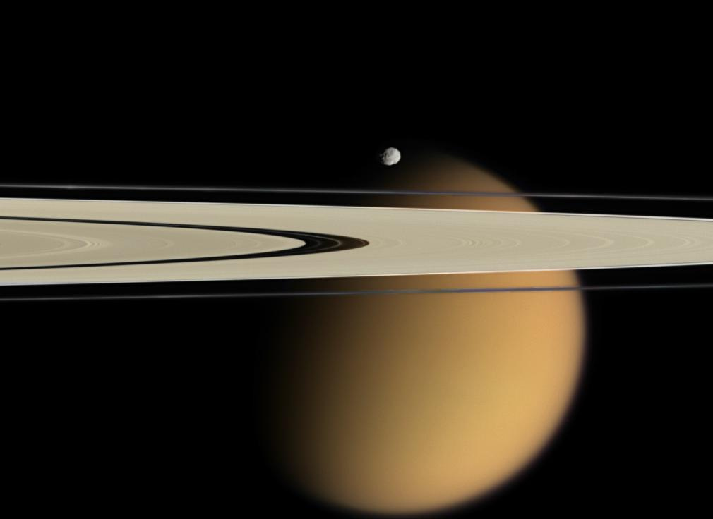 Saturn's orange moon Titan peeks from behind two of Saturn's rings. Small, battered Epimetheus, another of Saturn's 62 moons,