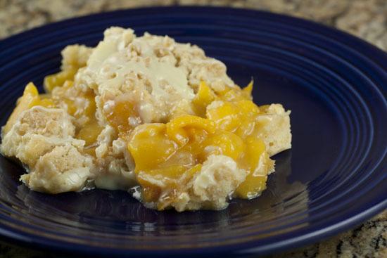 "<strong>Get the <a href=""http://www.macheesmo.com/2011/09/white-chocolate-peach-cobbler/"">White Chocolate Peach Cobbler recip"