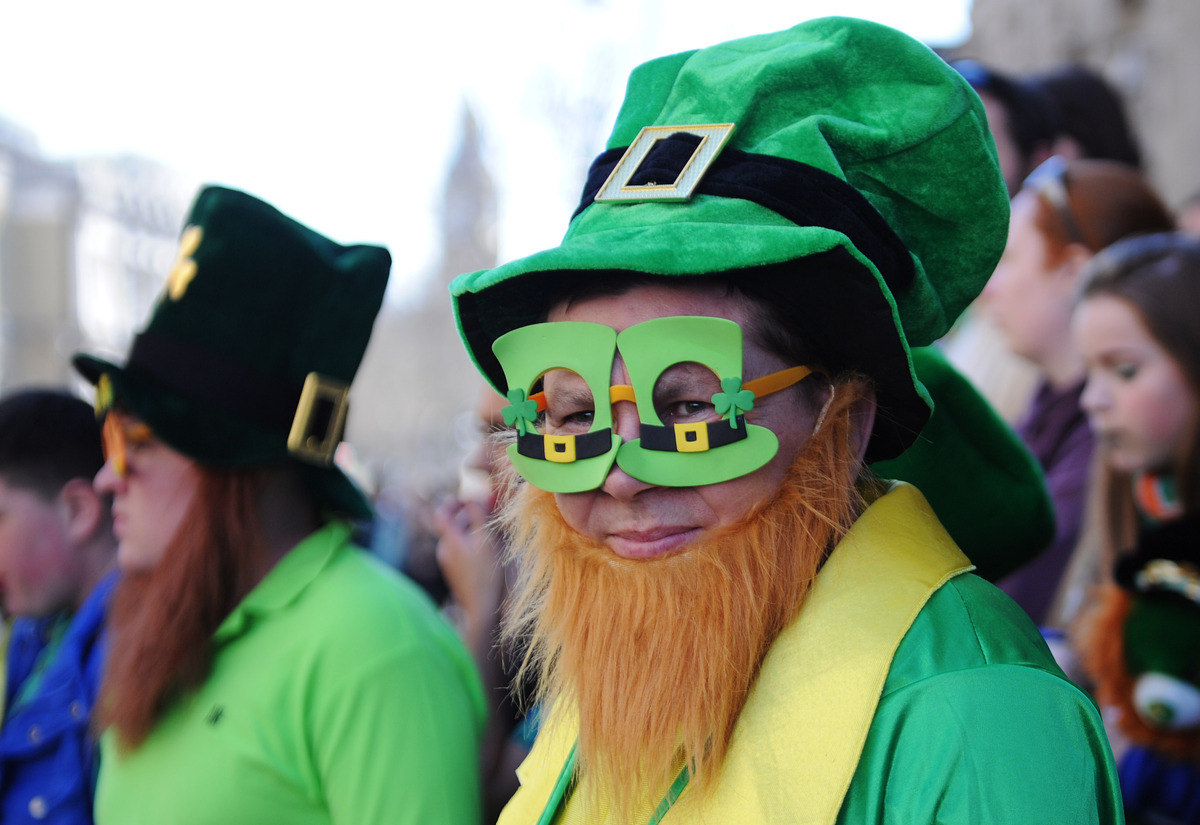 A man dressed in an Irish themed costume watches the annual St Patrick's Day Festival pass from Piccadilly to Trafalgar Squar