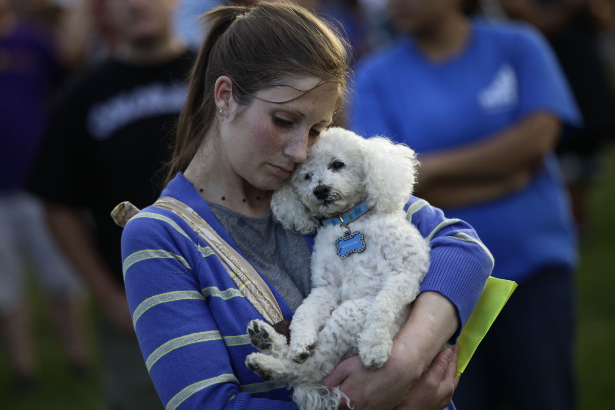 A woman hugs her dog during a memorial outside the Aurora Municipal Center July 22, 2012 in Aurora, Colorado.