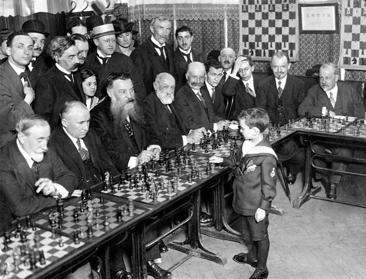 "Chess prodigy Samuel Reshevsky, aged 8, defeating several chess masters in France in 1920. <em>Credit: <a href=""http://en.wik"