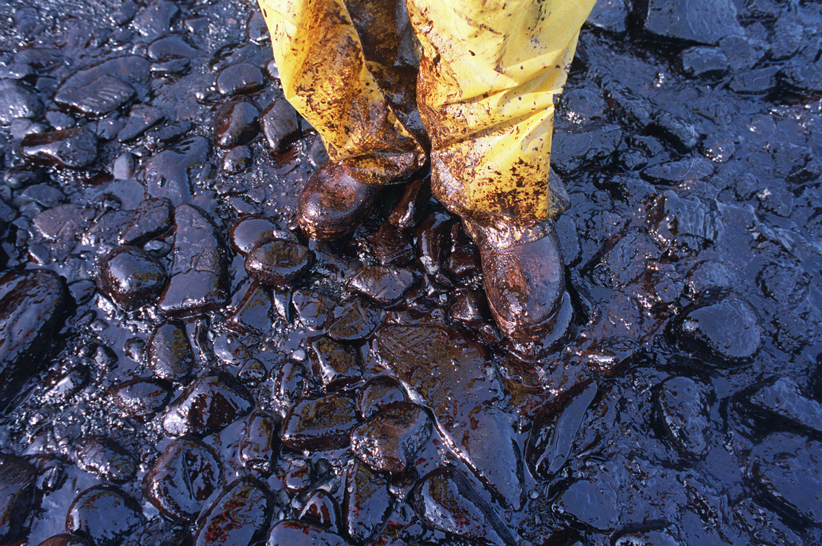 Thick crude oil washed up on the cobble beach of Evans Island sticks to the boots and pants of a local fisherman in Prince Wi