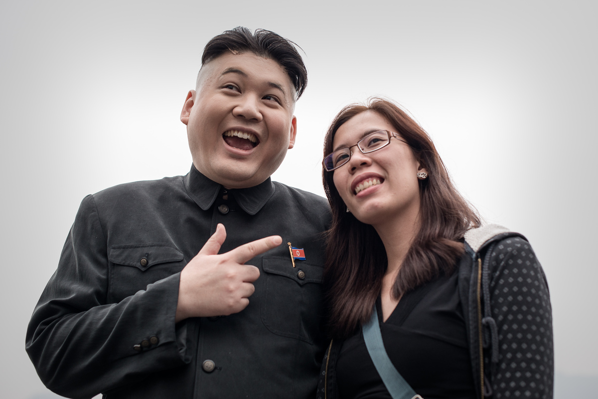 Hong Kong born Australian named Howard (L) and impersonator of North Korean leader Kim Jong-Un poses with a tourist in Hong K