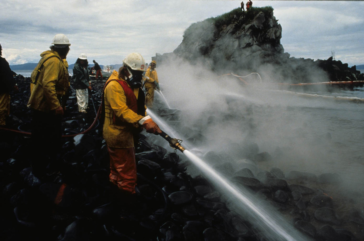 Spill workers, one wearing a respirator, hose beach during a Corexit application test on Quayle Beach, Smith lsland (Prince W