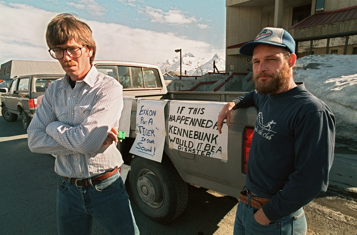 Fishermen Greg Will (L) and Matt Kinney, both of Valdez, stand in protest outside an Exxon news conference room which was clo