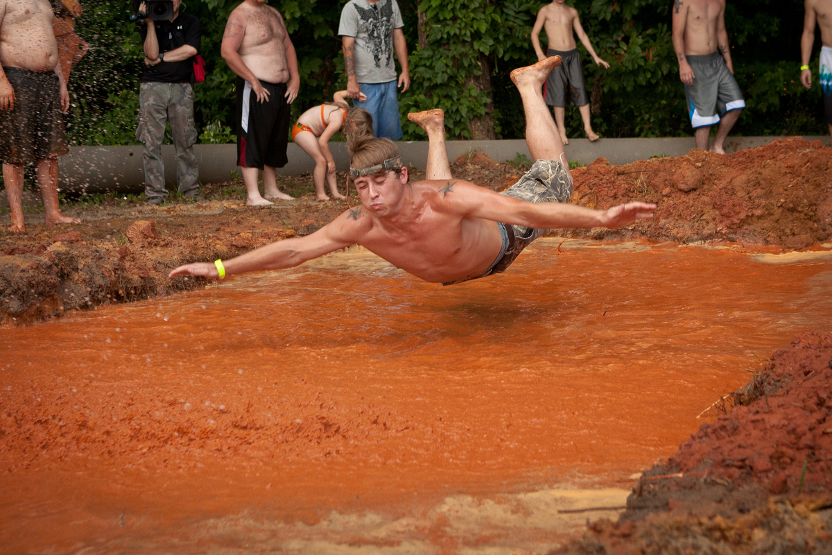 A competitor in the Summer Redneck Games takes a belly flop into a mud pit during competition on May 26, 2012 in East Dublin,