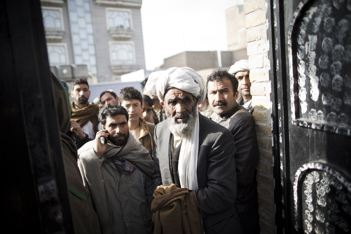 Afghan residents gather outside a closed voter registration center to try to receive their voter cards a day after registrati