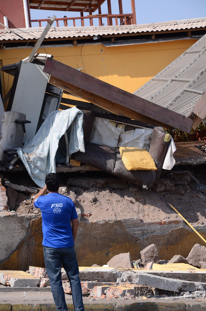 A man lloks at a destroyed house in Iquique, northern Chile, on April 2, 2014 a day after a powerful 8.2-magnitude earthquake