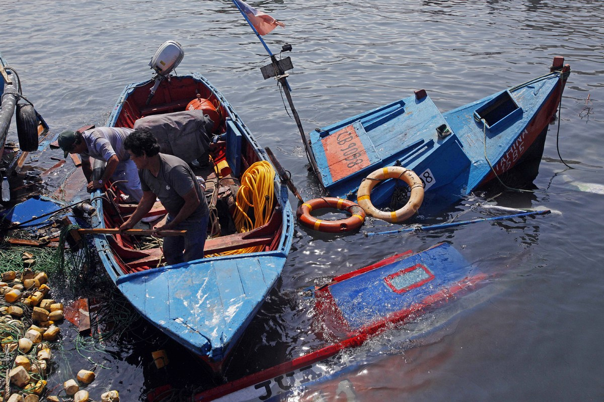 Fishermen look to salvage any remains destroyed overnight in the port of Iquique, in northern Chile, on April 2, 2014 after a