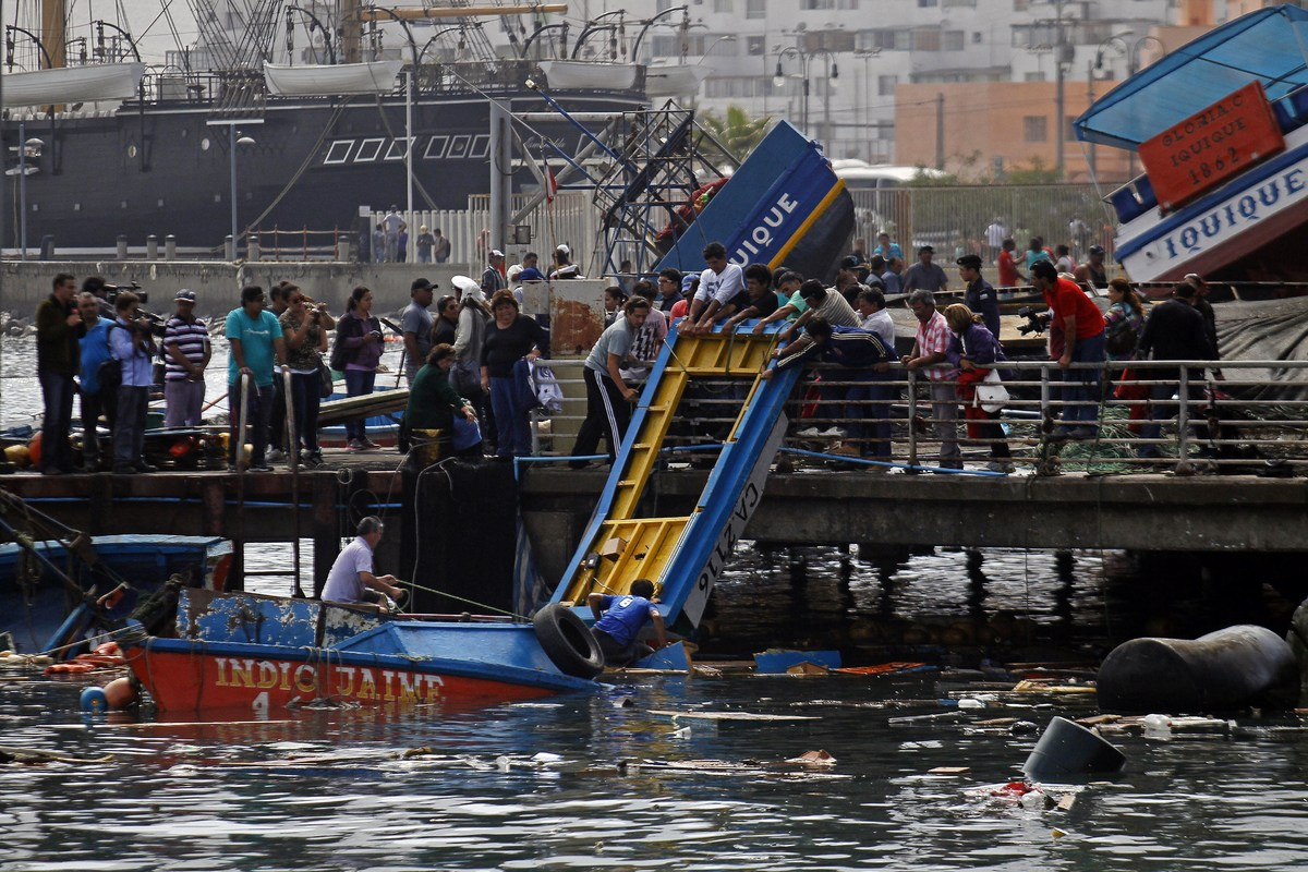 Fishermen try to salvage any remains destroyed overnight in the port of Iquique, in northern Chile, on April 2, 2014 after a