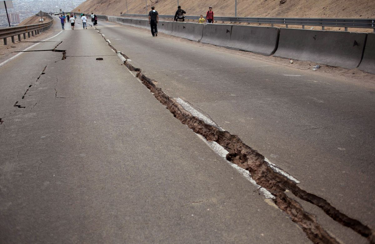 People walk along a road damaged by a powerful 8.2-magnitude earthquake that hit off Chile's Pacific coast, in Iquique, north