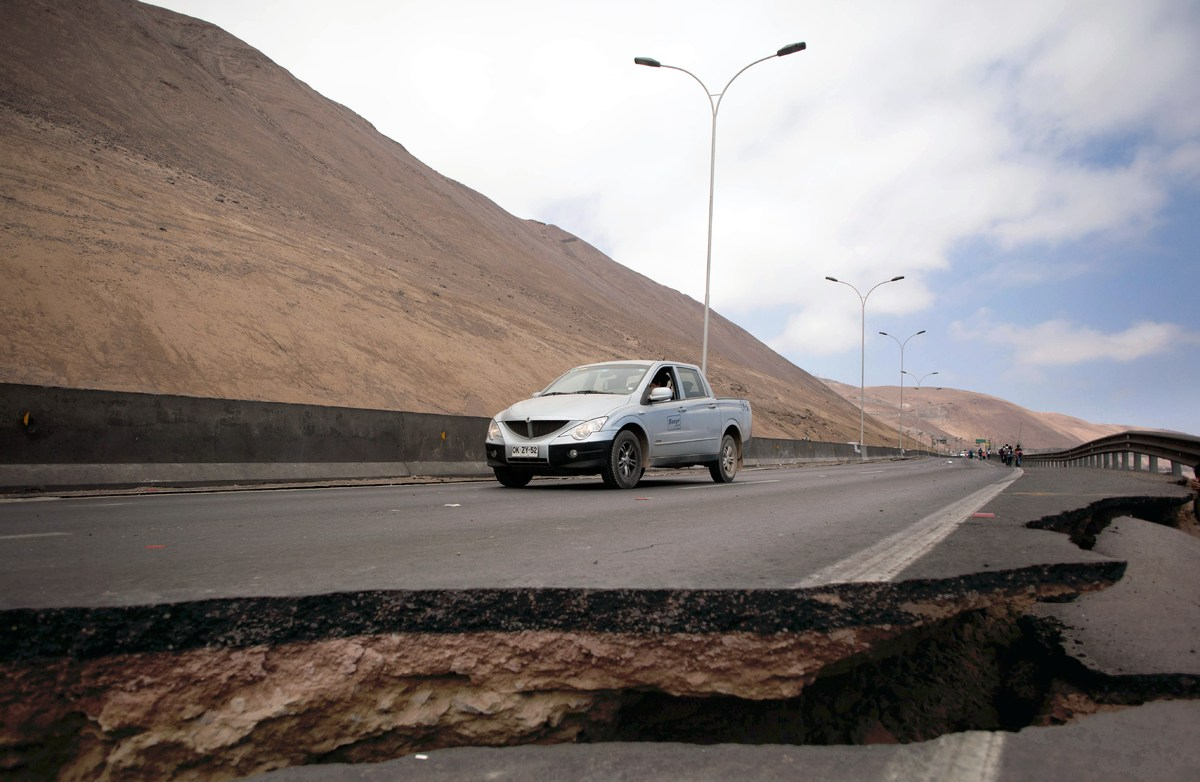 A car stops by a crack on a road damaged by a powerful 8.2-magnitude earthquake that hit off Chile's Pacific coast, in Iquiqu